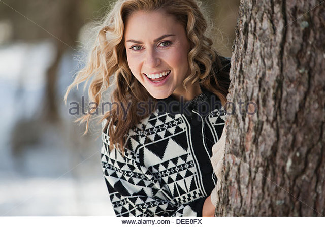 Woman peeking out from behind tree - Stock Image