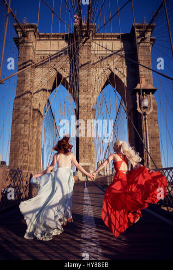 Two young women in blue and red gowns on the Brooklyn bridge running happily away from the camera in New York city - Stock Image
