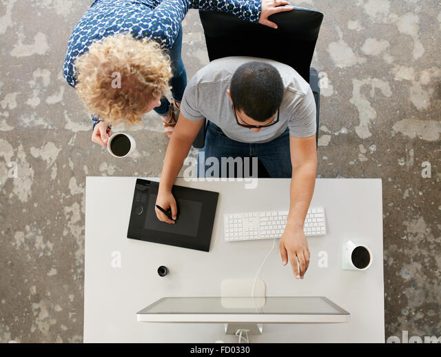Top view of young graphic designers working in office. Using digitized graphic tablet, digitized pen and desktop - Stock-Bilder