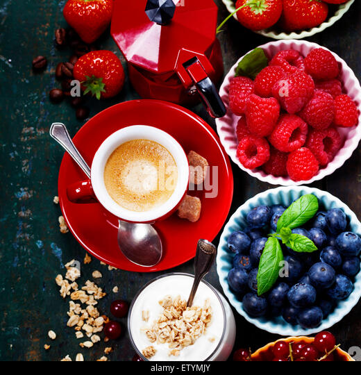 Healthy breakfast - yogurt with muesli and berries - health and diet concept. Blue background - Stock Image
