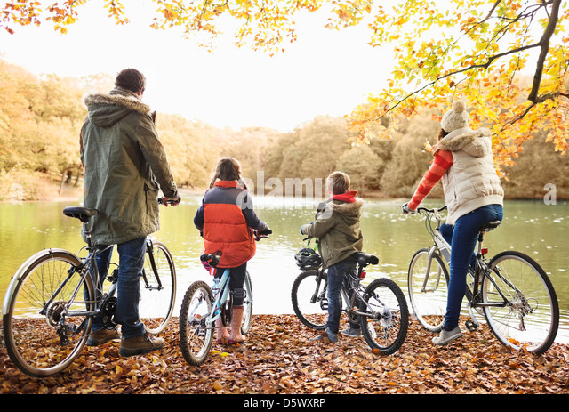 Family sitting on bicycles together in park - Stock-Bilder