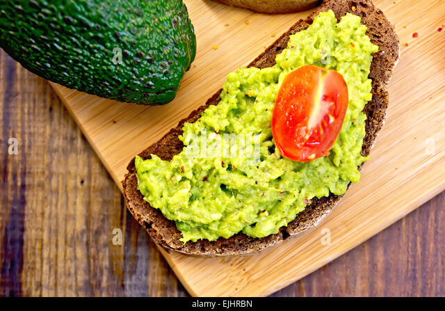 Sandwich with guacamole avocado and tomato on board - Stock Image