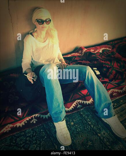 Full Length Of Young Woman With Cigarette Sitting On Carpet At Home - Stock-Bilder
