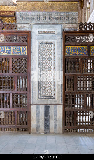 Architectural detail of a decorative mosaic marble colored panel between interleaved perforated wooden walls (Mashrabiya), - Stock Image