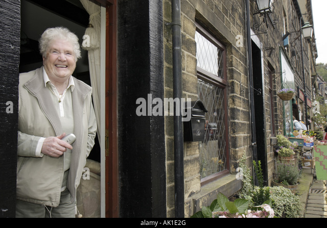 UK, England, Haworth, Main Street, smiling senior woman, resident, doorway, - Stock Image