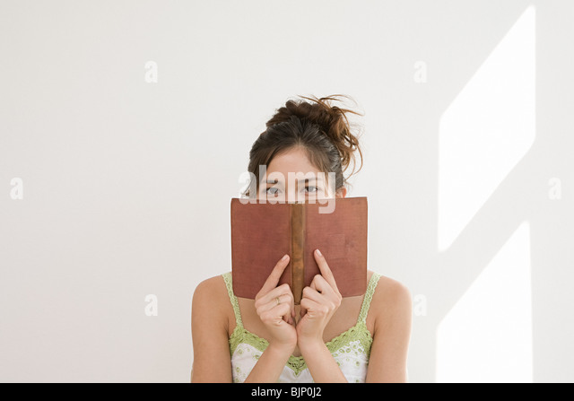 Woman hiding behind a book - Stock Image