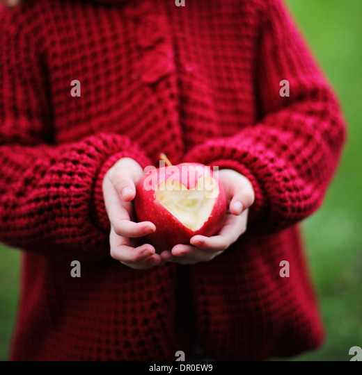 Child holding a red apple with heart shape - Stock-Bilder
