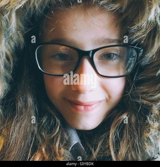 Girl with glasses in fur lined hood - Stock Image