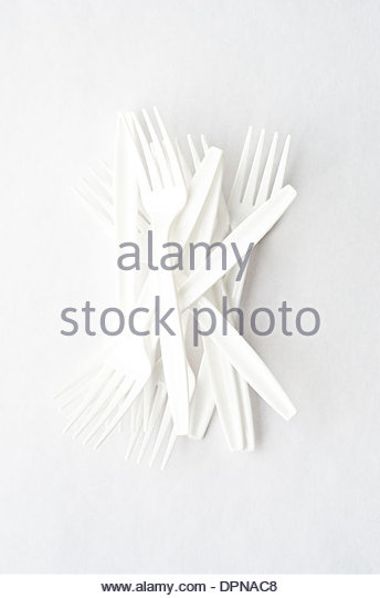Pile of white plastic forks in different directions shot from above on white background. - Stock Image