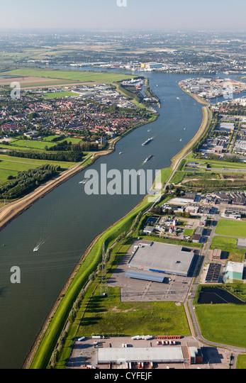 The Netherlands, Dordrecht, boats in river called Dordtse Kil. Left the village of 's-Gravendeel. Right industrial - Stock Image