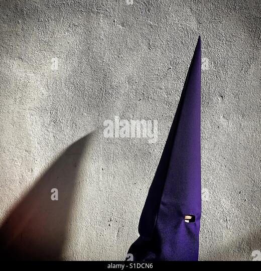 A penitent wearing a pointed hood walks during an Easter Week procesion in Baeza, Jaen province, Andalusia, Spain - Stock Image