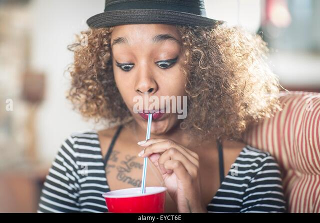 Portrait of young woman pulling a face whilst drinking soft drink - Stock Image