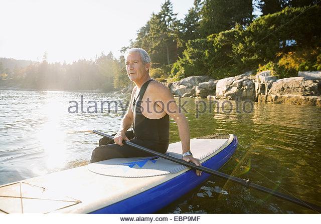 Senior man sitting on paddle board in ocean - Stock Image