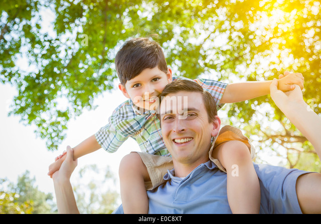 Mixed Race Father and Son Playing Piggyback Together in the Park. - Stock Image