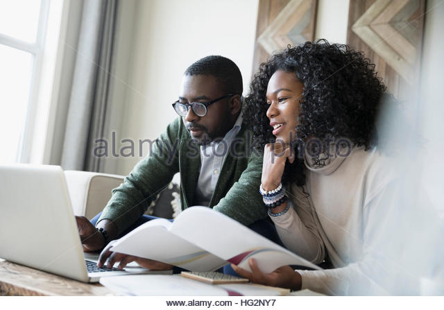 Couple with laptop reviewing investment portfolio online - Stock Image