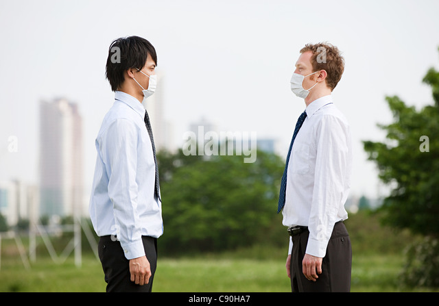 Two businessmen wearing pollution masks, face to face - Stock Image