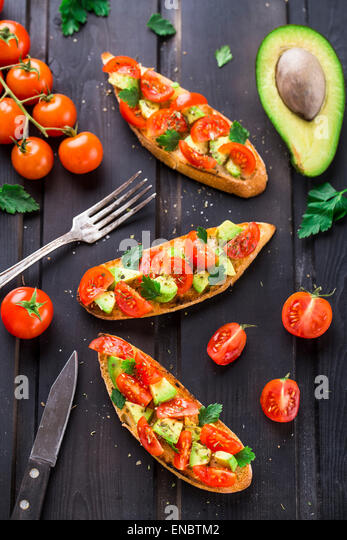 Bruschetta with tomato, avocado and herbs on a black wooden table - Stock Image