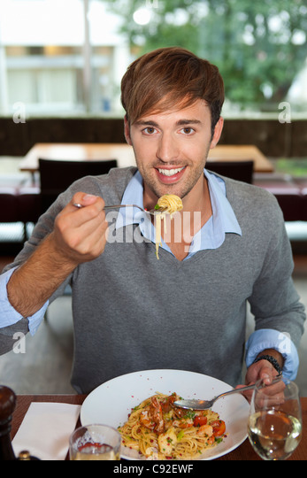 Man eating pasta in restaurant - Stock Image