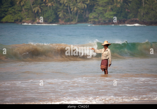 fisherman angling in the waves of Mirissa beach, Sri Lanka - Stock Image