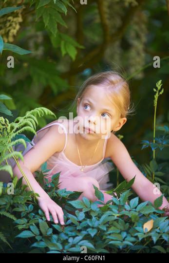 Girl in ballet costume hiding in bush - Stock Image