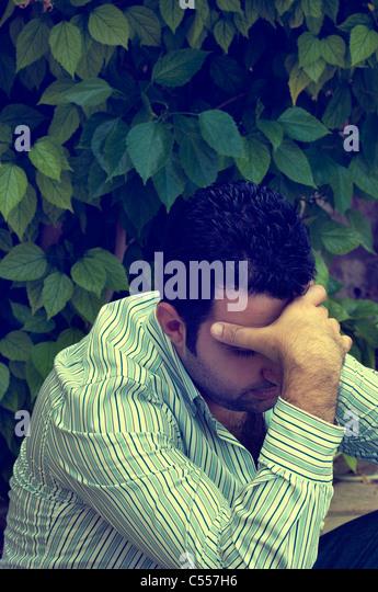 Depressed man head in hands - Stock Image