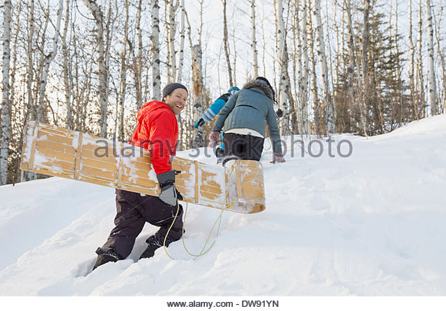 Family walking up hill with toboggan - Stock Image