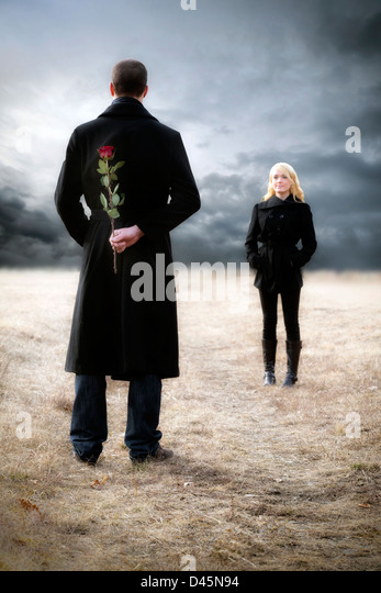 a man hides a red rose to surprise his girlfriend - Stock-Bilder