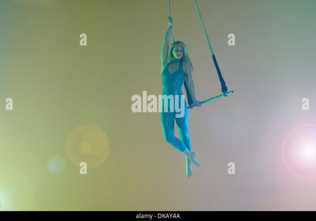 Trapeze artist holding trapeze - Stock Image