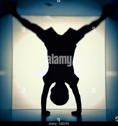 Silhouette of a boy standing on hands - Stock Image