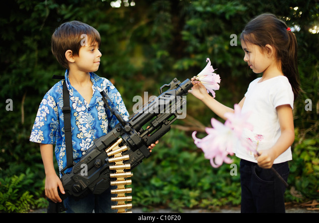 Five year old girl places flowers in barrel of her brother's toy machine gun - Stock-Bilder