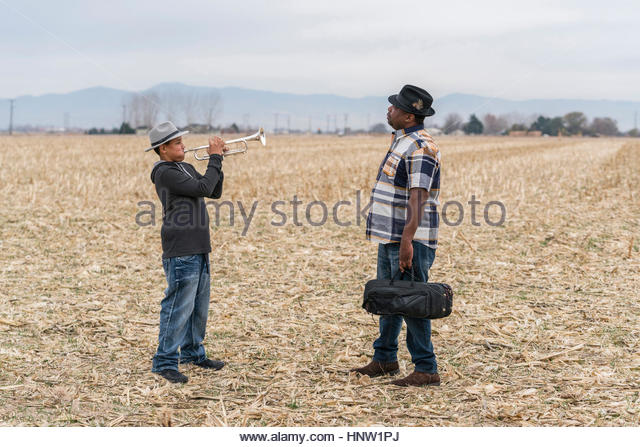 Father watching son playing trumpet in field - Stock-Bilder