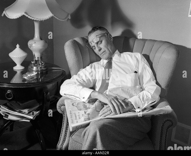 1950s MIDDLE AGED MAN ASLEEP IN CHAIR READING NEWSPAPER EYE GLASSES PUSHED UP ON FOREHEAD - Stock Image