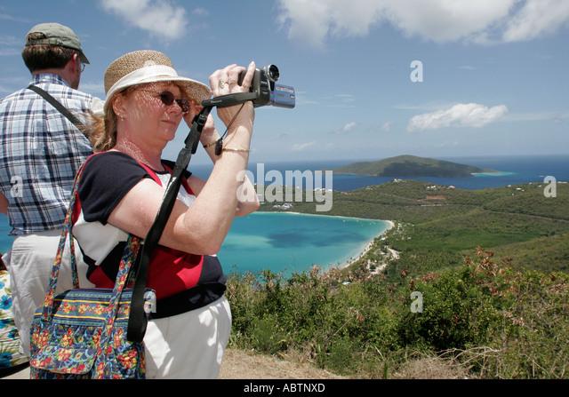 St. Thomas USVI North Side Skyline Drive Megans Bay Overlook Atlantic Ocean woman video recorder - Stock Image