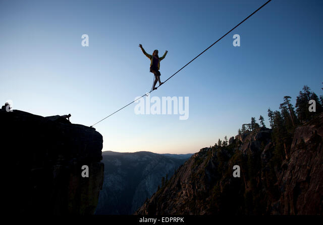 Silhouette of professional highliner Hayley Ashburn walking a highline above the Yosemite Valley floor at Taft Point - Stock Image