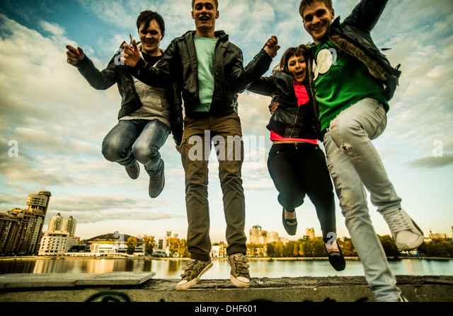 Four friends jumping mid air, Russia - Stock Image