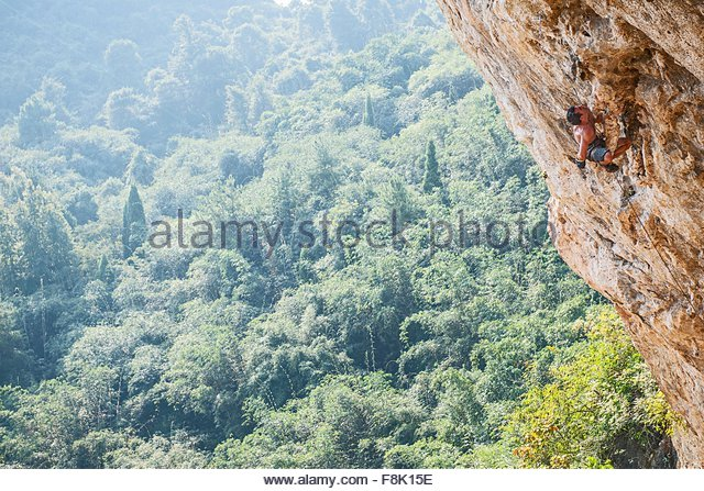 Male climber climbing Odin's Den next to Moon Hill in Yangshuo, Guangxi Zhuang, China - Stock Image