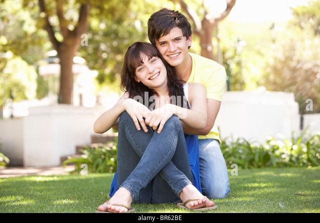 Portrait Of  Romantic Teenage Couple Sitting In Park - Stock-Bilder