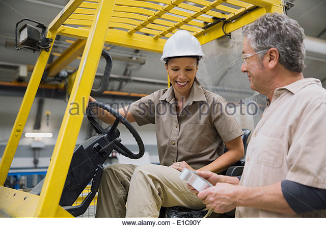 Workers at forklift examining metal part - Stock Image