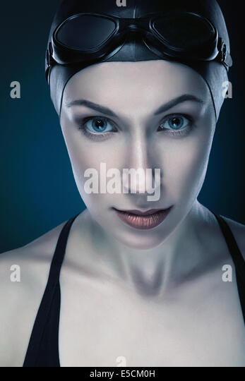 close-up vertical portrait of swimmer in dark blue - Stock Image