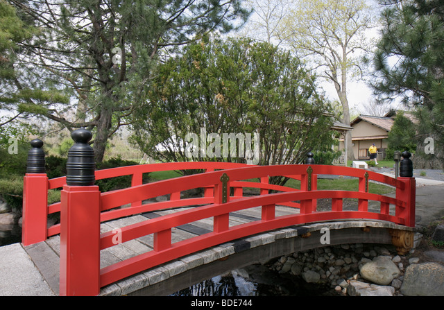 Michigan Saginaw Japanese Cultural Center & and Tea House Asian inspired arching bridge vermillion red stream - Stock Image