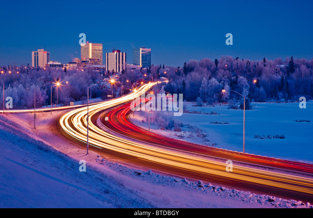 Twilight view of traffic on Minnesota Blvd. with downtown Anchorage in the background, Southcentral Alaska, Winter - Stock Image