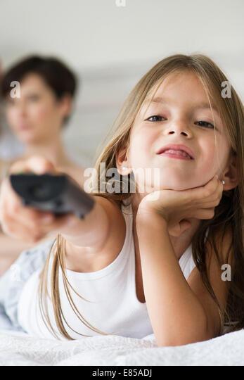 Little girl holding remote control - Stock-Bilder