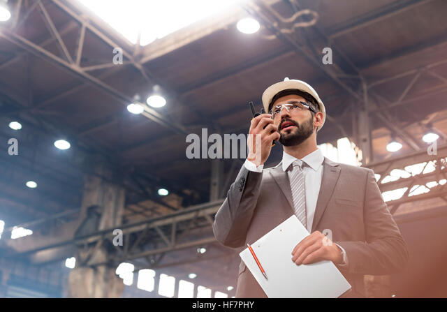 Manager with walkie-talkie in steel factory - Stock Image