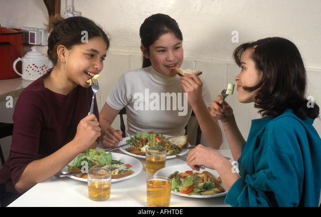 3 young teenage girls eating healthy food - Stock Image