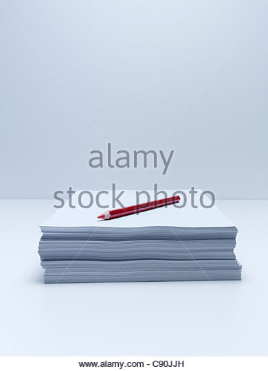 Red pencil on stack of paper - Stock Image