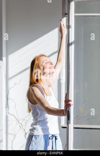Woman opening window. - Stock Image