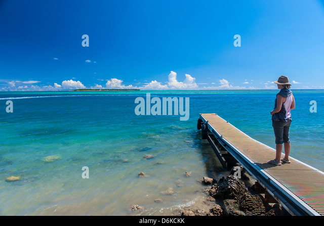 Tourist standing on a little pier with Cocos Island in the distance, Guam, US Territory, Central Pacific, Pacific - Stock Image
