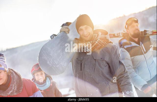 Portrait smiling snowboarder friends carrying snowboards - Stock-Bilder