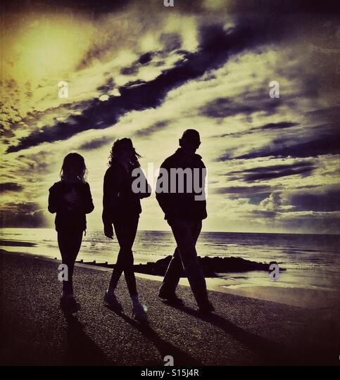 Three people in silhouette walking along beside the sea (adult and two children) - Stock-Bilder