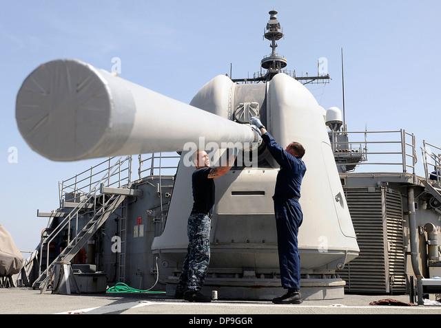 U.S. Sailors perform maintenance on a Mk 45 5-inch lightweight gun on the USS Bunker Hill - Stock Image